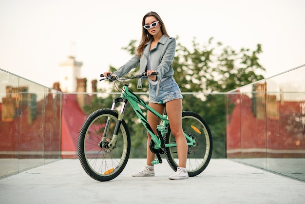 패션 청바지 옷을 입고 매력적인 유혹 어린 소녀는 자전거에 앉아서 여름 저녁에 카메라에 포즈 세련 된 안경을 착용합니다.