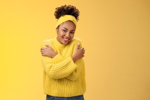 Attraente tenera ragazza afro-americana dolce in maglione fascia che si abbraccia le mani toccano le spalle si sentono caldo sicuro accogliente sorridente felicemente abbracciando coccole bella risatina. copia spazio