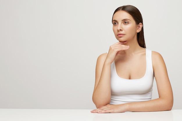 Привлекательная нежная женщина с идеальной здоровой свежей кожей сидит за столом, смотрит в сторону