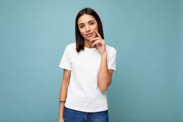 カジュアルな白いtシャツで魅力的な思考の若い女性