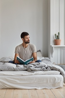 Attractive thoughtful bearded man with pensive expression, looks away, sits on bed, holds book,