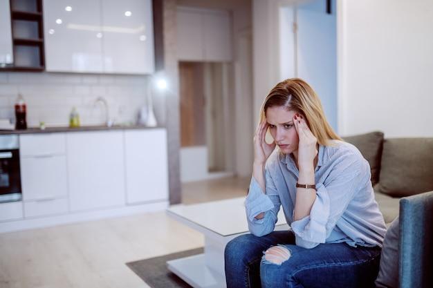 Привлекательная продуманная кавказская белокурая женщина, сидящая на диване в гостиной и имеющая депрессию.