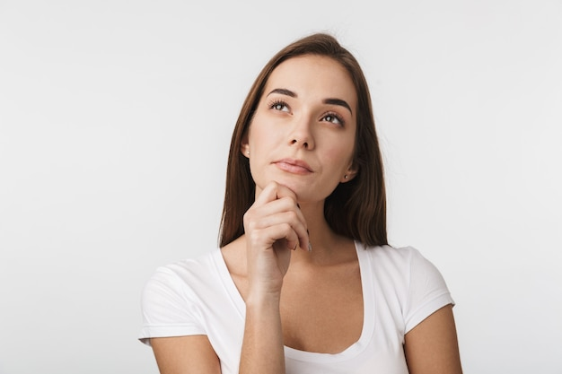 Attractive thoughtful young woman standing isolated over white wall