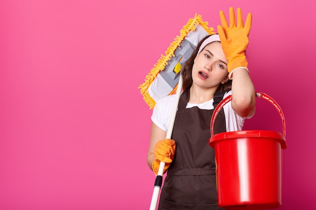 Attractive tired young female keeps hand on forehead, puts mop on shoulder.