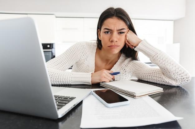 キッチンに座ってラップトップコンピューターとドキュメントで作業する魅力的な疲れた若い女性