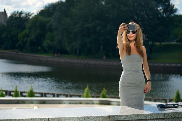 Attractive tourist girl making selfie with river bank on background in city park