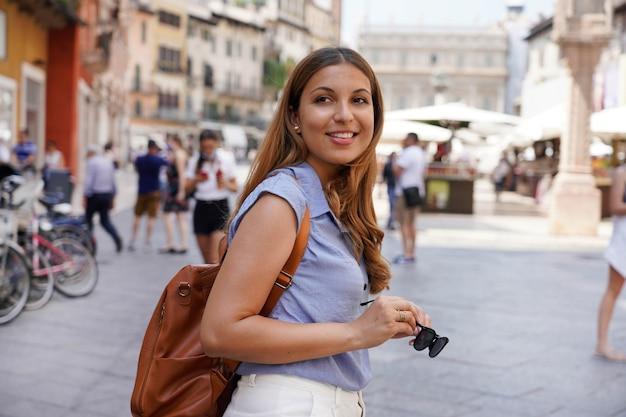 路上でサングラスを保持している魅力的な観光客の女性、夏のファッションスタイル、ヨーロッパへの旅行