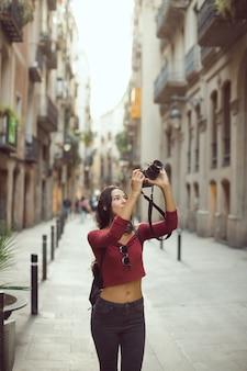 도시 거리에서 야외 dslr 카메라로 이미지를 촬영하는 매력적인 관광 여자 사진 작가
