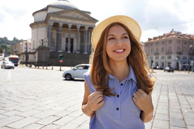Привлекательная девушка путешественника прогулки в турине с церковью gran madre di dio на заднем плане. туристическая девушка, идущая в турине, италия.