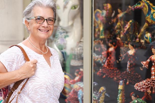 バルセロナを訪れる魅力的な旅行者の年配の女性。ショーウィンドウで芸術作品を探しています。休暇を楽しんで幸せな引退