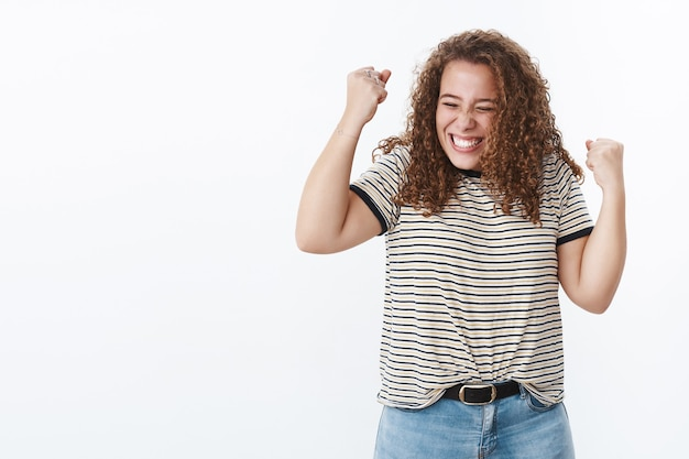 Attractive triumphing chubby cute girl close eyes smiling delighted lift clenched fists up sky victory celebration gesture achieve goal receive best news, good results