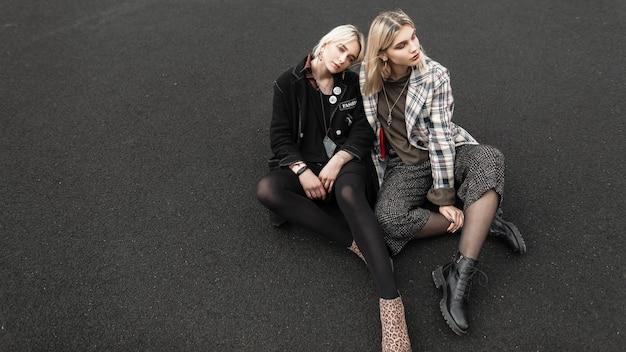 街の遊び場に座る美しいカジュアルな服装の魅力的な双子の姉妹