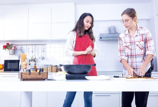 Привлекательные две улыбающиеся женщины готовят на современной кухне, два друга веселятся, сестры готовят вместе.