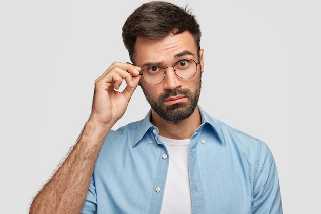Attractive unshaven male looks curiously through glasses, keeps hand on rim, dressed in fashionable shirt, poses against white wall. young man listens something interesting with wonder