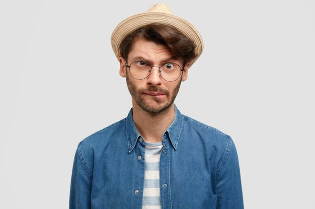 Attractive unshaven man bites lips and looks with bewilderment, has unexpected look, dressed in fashionable straw hat, denim shirt, stands indoor against white wall