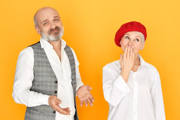 Attractive unshaven man with bald head having frustrated mournful expression, making helpless gesture, his beautiful stylish mature wife looking up in surprise, covering mouth with hand, gasping