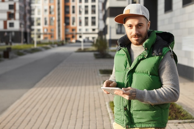 Attractive unshaven young male in snapback staying always connected, messaging friends online using phone outside on city street. cute hipster guy typing message on touch pad