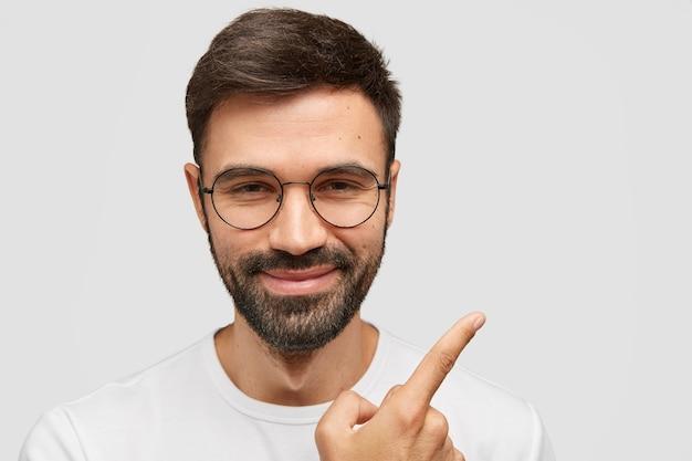 黒髪と剛毛の魅力的な無精ひげを生やした若い男は、人差し指で示す満足のいく表現をしています