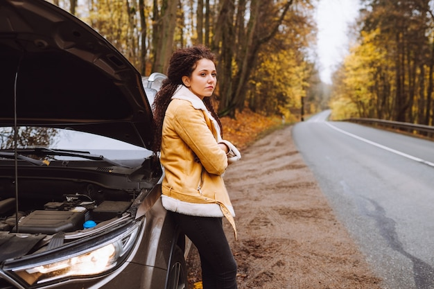 Attractive upset afro haired brunette beside of her broken car in the forest on empty road.