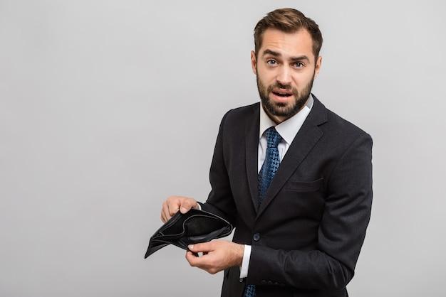 Привлекательный расстроенный молодой бизнесмен в костюме, стоящий изолированно над серой стеной, показывая денежные банкноты