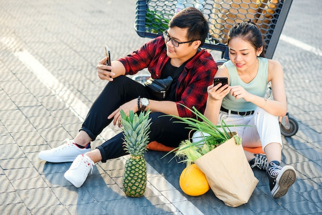 Attractive vietnamese boy and beauiful girl sitting on the parking near shopping mall and uses their smartphones.