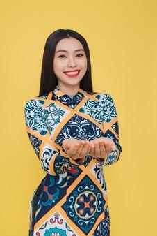 黄色の背景で隔離の伝統的な衣装を着て魅力的なベトナムの女性