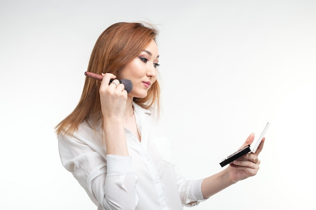 Attractive visagist or korean make-up artist holding a makeup brushes and a palette of eye shadow on white wall