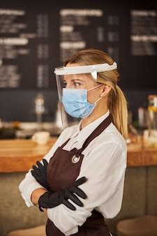 Attractive waitress working in quarantine in medical mask