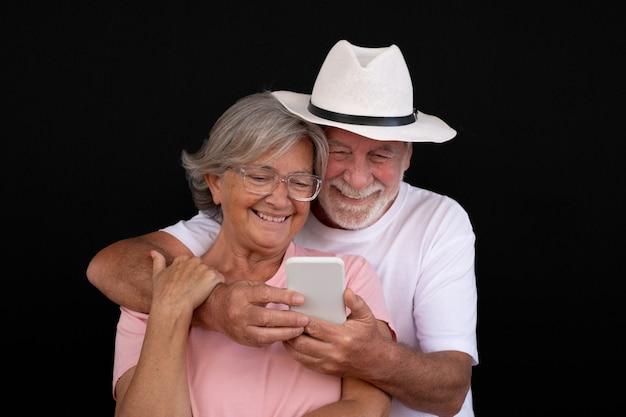 Привлекательные седые старшие пара обнялись с помощью мобильного телефона. два счастливых пенсионера, наслаждающиеся свободным временем и технологиями, новые молодые люди. черный фон