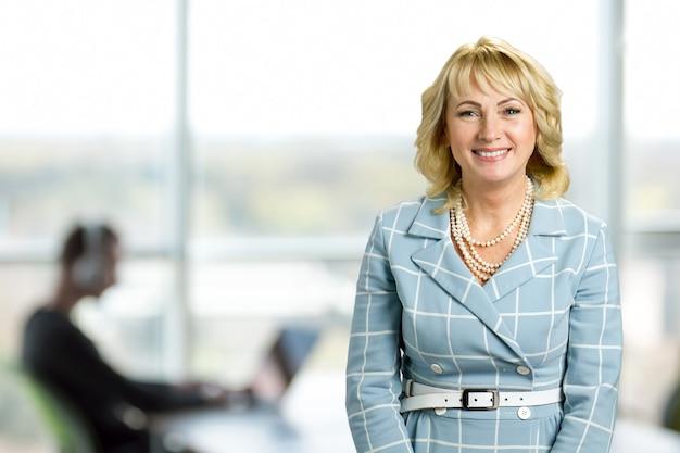 オフィスで魅力的な白い肌の女性。オフィスの窓に立っている笑顔の成熟した女性の肖像画。