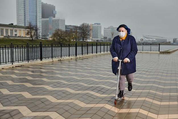 파란 머리를 가진 매력적인 백인 십 대 소녀는 의료 마스크와 산책로를 따라 스쿠터를 타고있다