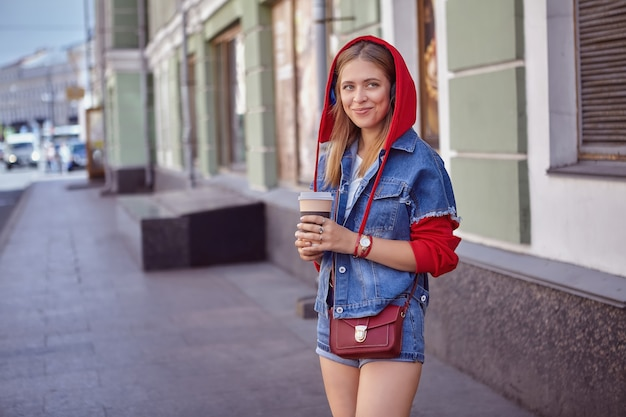 Attractive white young woman about 25 years old in shorts and hoodie is walking during street in saint-petersburg.