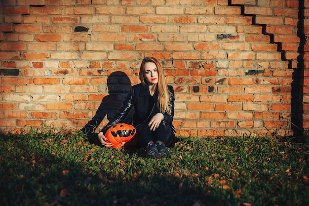Attractive witch holding pumpkin 'trick or treat'.