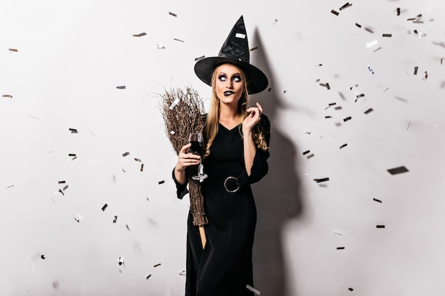 Attractive witch holding wineglass with blood. indoor photo of blonde lady in wizard costume posing under confetti in halloween.