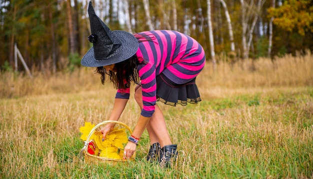 Attractive witch with pumpkin in the autumn forest. halloween party concept