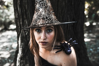 Attractive witch with spider on shoulder in forest datime