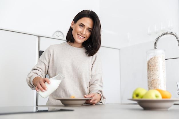Привлекательная женщина 30 лет готовит завтрак с овсянкой и фруктами, стоя на современной кухне дома