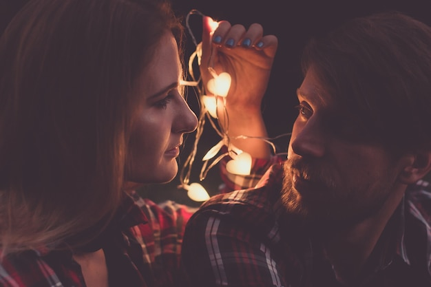 화환의 빛에 의해 서로 얼굴을 바라보는 매력적인 여자와 수염 남자