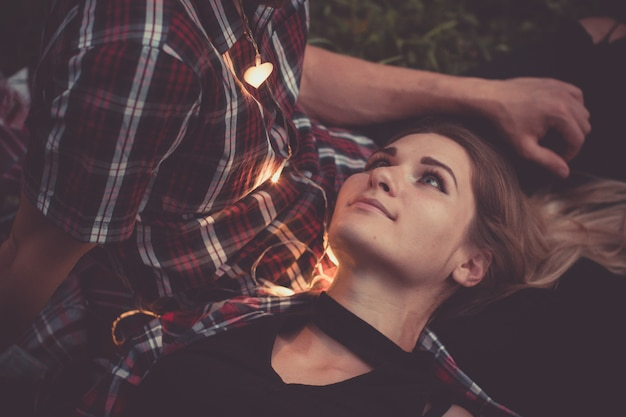매력적인 여자와 수염 남자는 화환의 빛에 의해 서로 얼굴을 찾고 야외 데이트