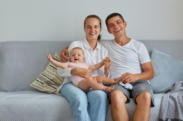 매력적인 여성과 잘생긴 여성이 유아 딸과 함께 소파에 앉아 카메라를 보며 웃고, 함께 행복하고, 집에 있는 가족, 실내 촬영.