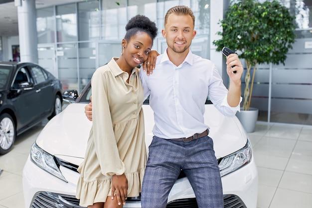 Привлекательная женщина и красивый парень довольны покупкой в автосалоне