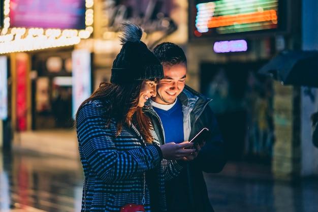 Привлекательная женщина и мужчина, улыбаясь с помощью телефона