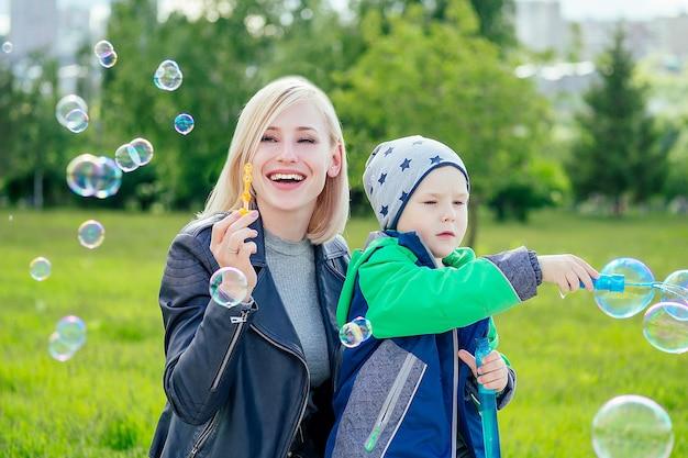 緑の草や木々を背景に公園でシャボン玉を吹く魅力的な女性と息子
