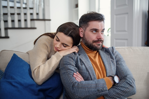 Attractive woman apologizing to frustrated man after quarrel, doubting boyfriend ignore, girlfriend feeling guilty, asking forgive her, begging pardon, admits mistake, regret, couple having problem