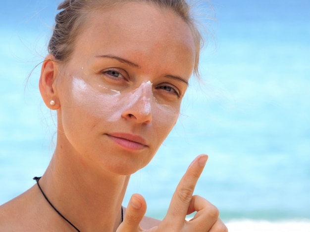 Attractive woman applies sunscreen on her face on a tropical beach.