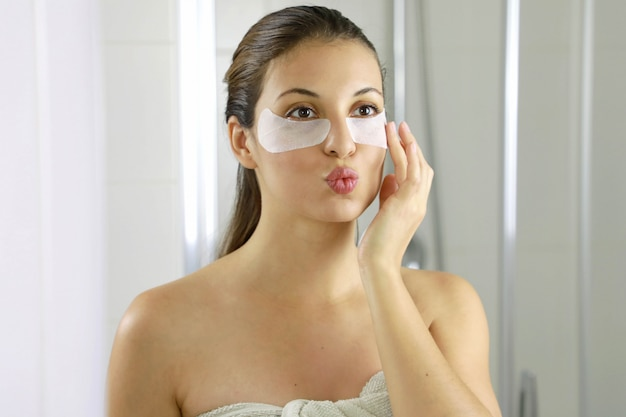 Attractive woman applying anti-fatigue under-eye mask looking and kissing herself in the mirror in the bathroom.