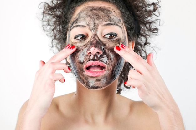 An attractive woman applying black face mask with her fingers against white background