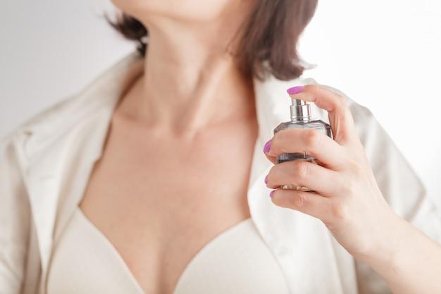 Attractive woman applying perfume
