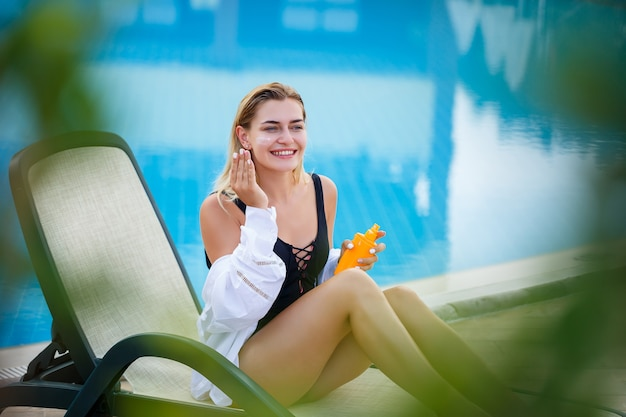 Attractive woman applying sunscreen on her face by the pool. vacation sun protection factor