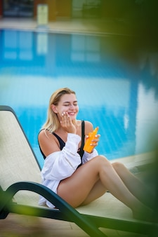 プールサイドで顔に日焼け止めを塗る魅力的な女性。休暇の日焼け止め係数